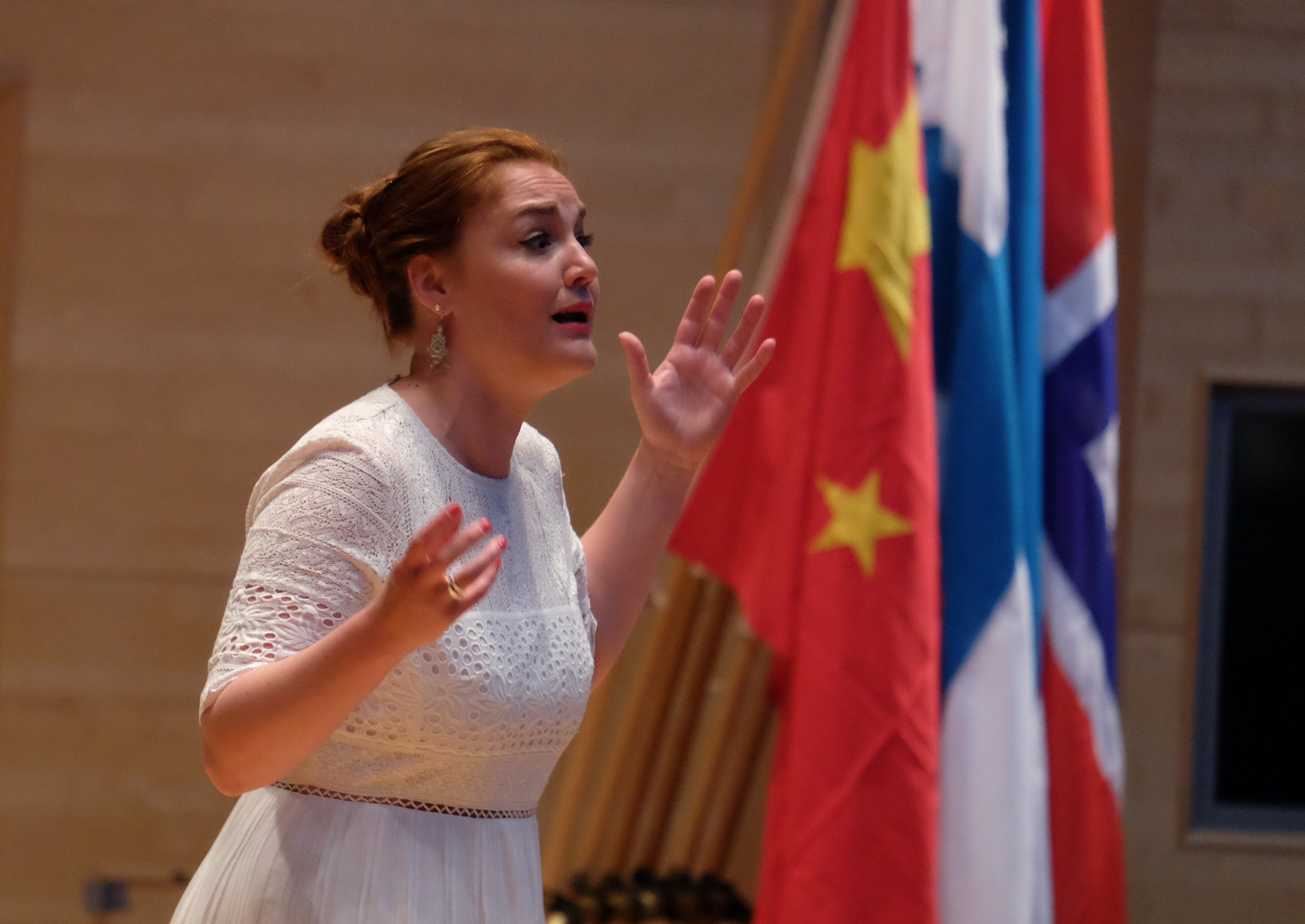 Woman singing with flags in the background